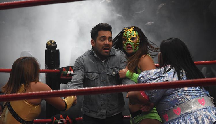 tres luchadoras tienen a Adán en el atrapado en un ring.